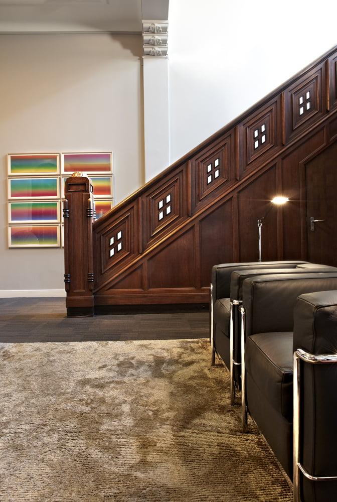 Interieur foto kantoor Schaap Rotterdam - ontvangstruimte met klassieke houten trap en zwart leren Le Corbusier LC2 fauteuils op hoogpolig goudkleurig vloercarpet