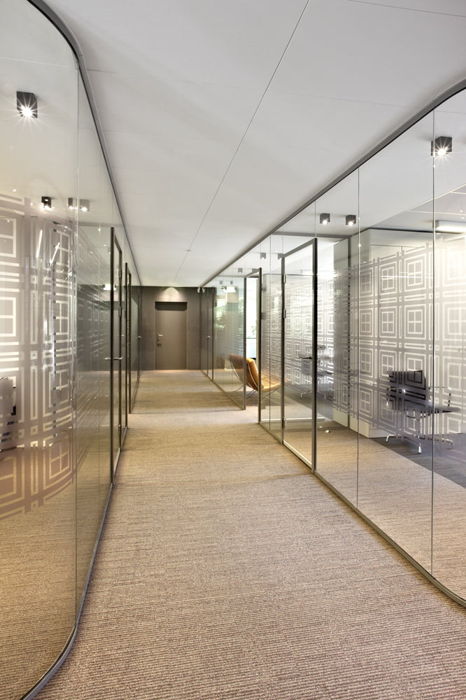 Interieur foto kantoor Schaap Rotterdam - Gang met aan weerszijden kantoren afgescheiden door glaswanden, voorzien van gefigureerde privacy folie, zonder verticale profielen en glazen deuren in combinatie met halfronde hoeken van volledig glas