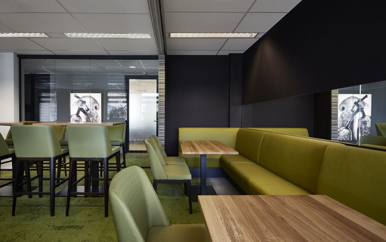 Interieur foto kantoor KCB Zoetermeer - lunchruimte met zit/statafel  en langen eetbank langs wand met spiegel. Op de achtergrond viltstroken wand en ledpaneel met vruchtenafbeelding