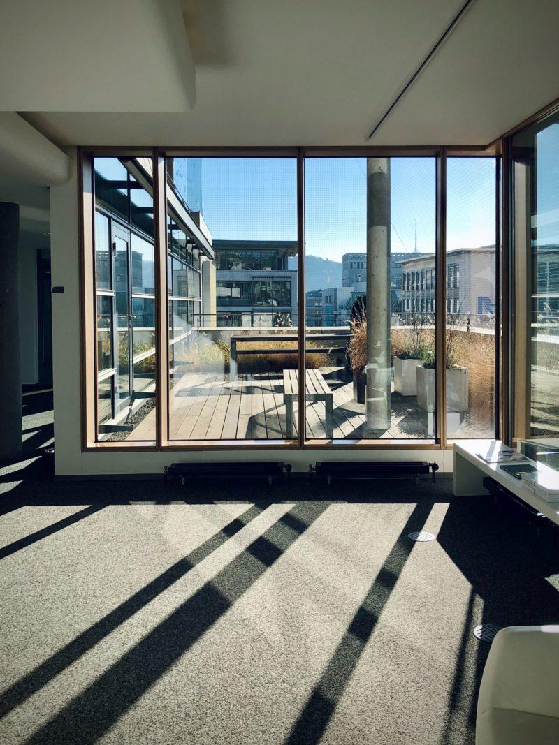 Interieurfoto vanuit de bovenste verdieping van een kantoor naar buiten op Schiphol-Rijk met uitzicht op het dakterras en omliggende kantoren