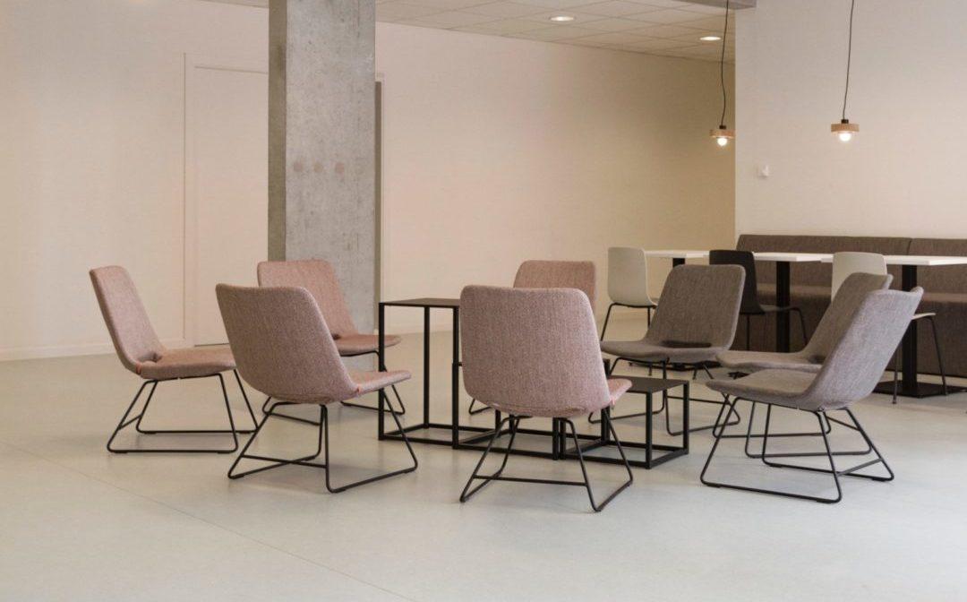 Interieurfoto van een moderne zit/ overleghoek met 7 moderne fauteuils in een kale kantine van een kantoor
